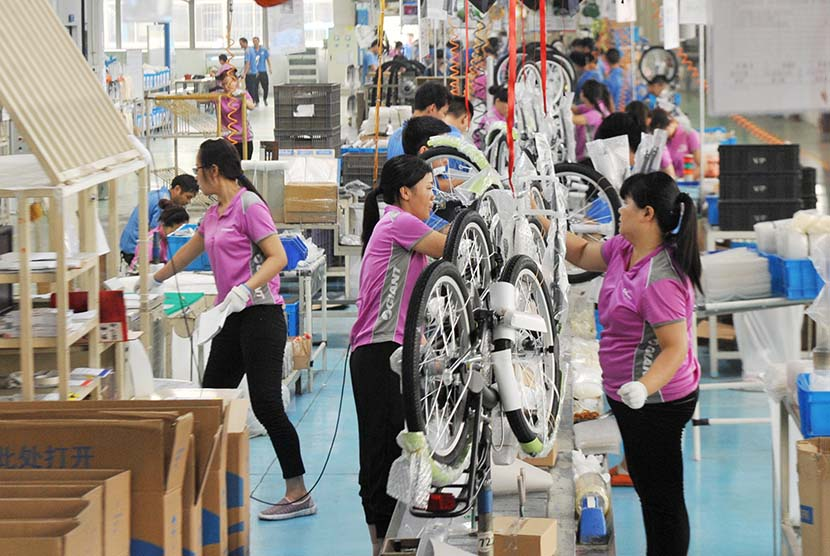 Young women work on a production line at a bike factory in Suzhou, Jiangsu province, Aug. 6, 2017. People Visual